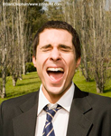 Picture of a businessman yelling outdoors at the top of his lungs. The man has his eyes closed and his mouth wide open. Rows of trees behind the man.